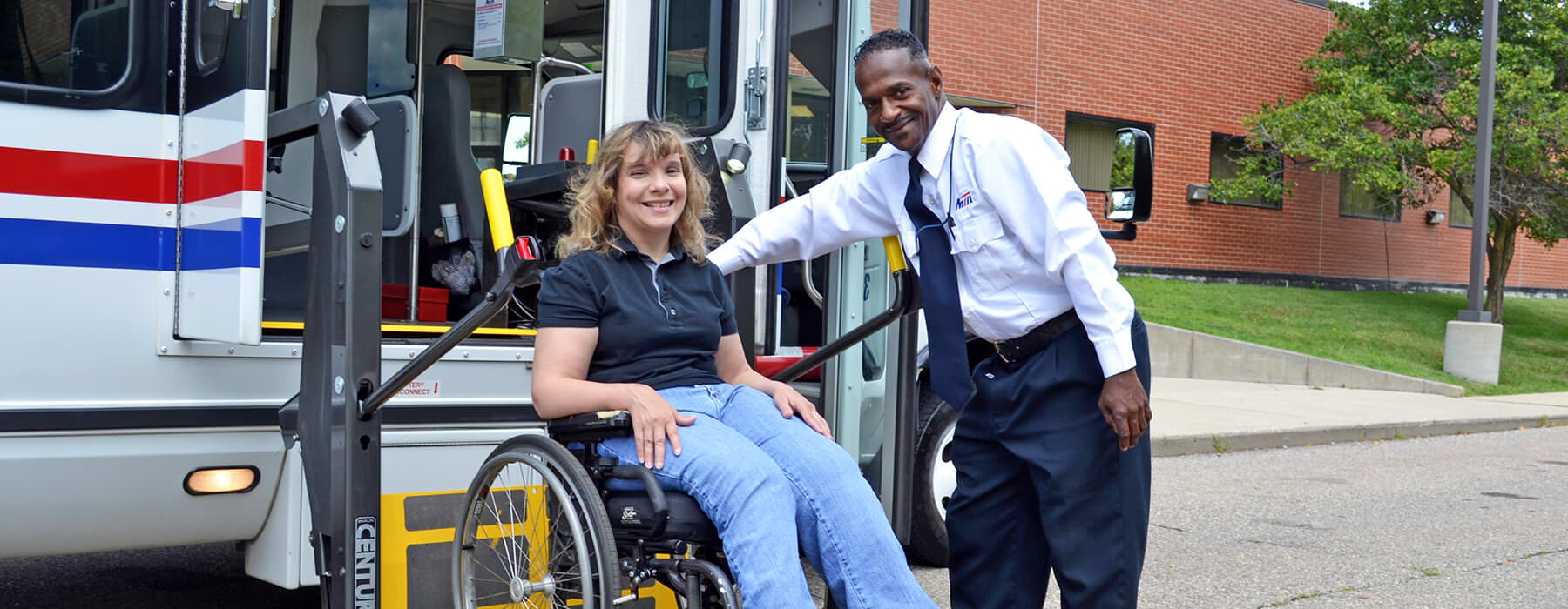 Woman in wheelchair exiting Your Ride bus using the wheelchair lift assisted by the driver.