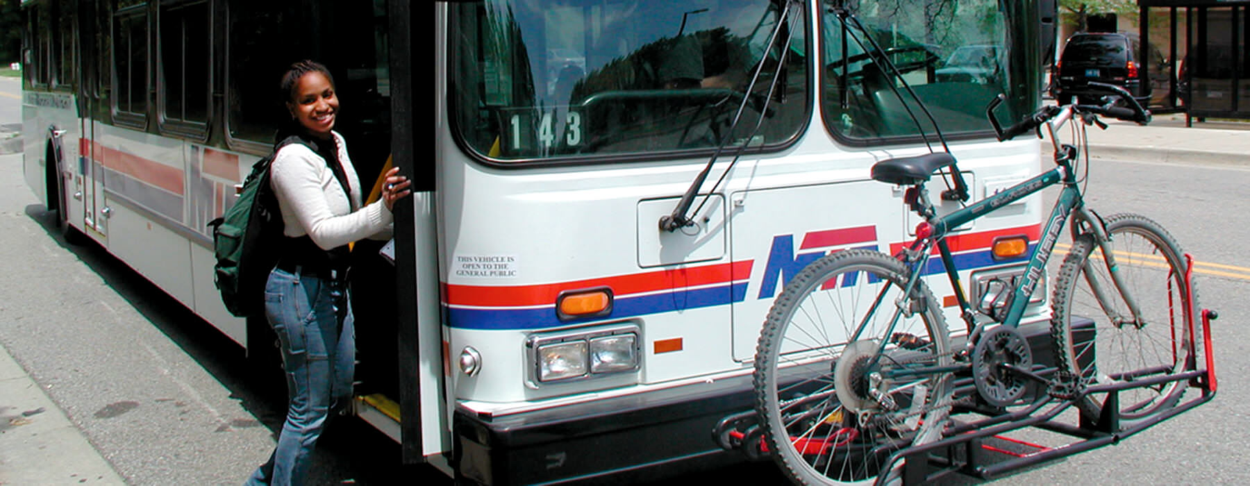 Woman boarding MTA Primary Route bus with bike on the rack in the front of bus.
