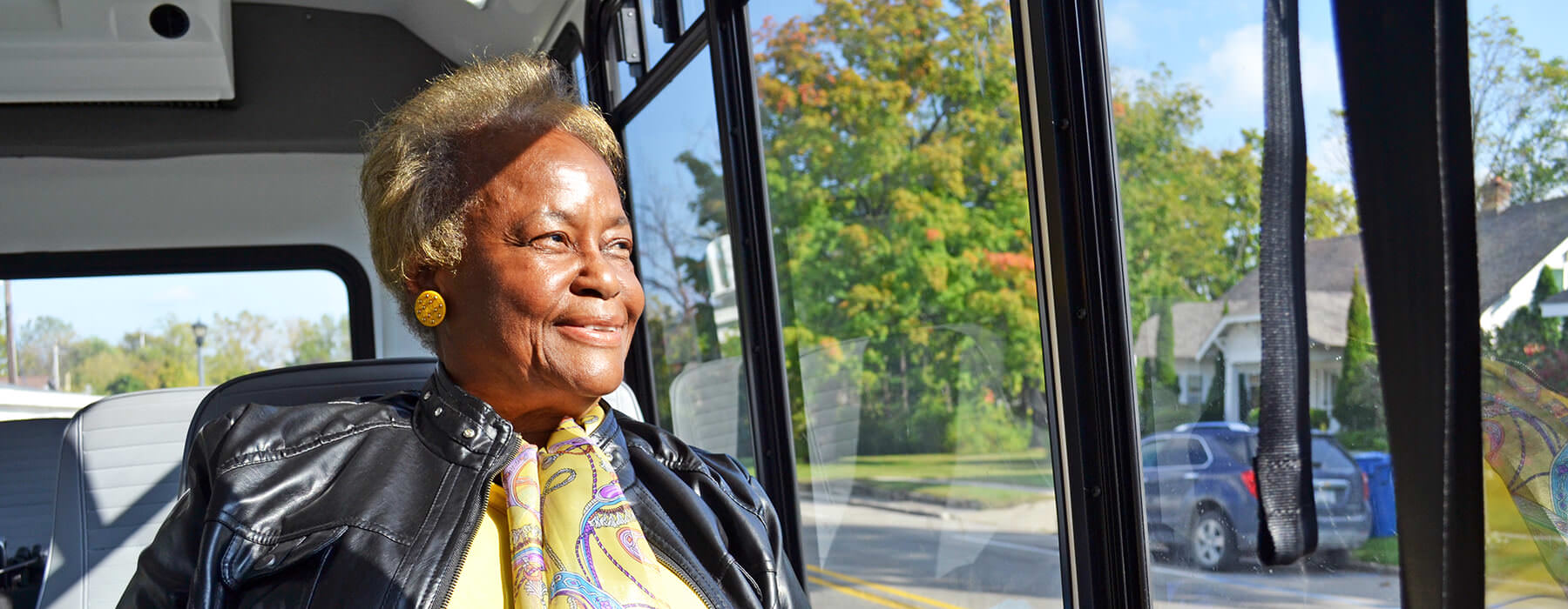 Smiling elderly woman looking out window of Your Ride bus.