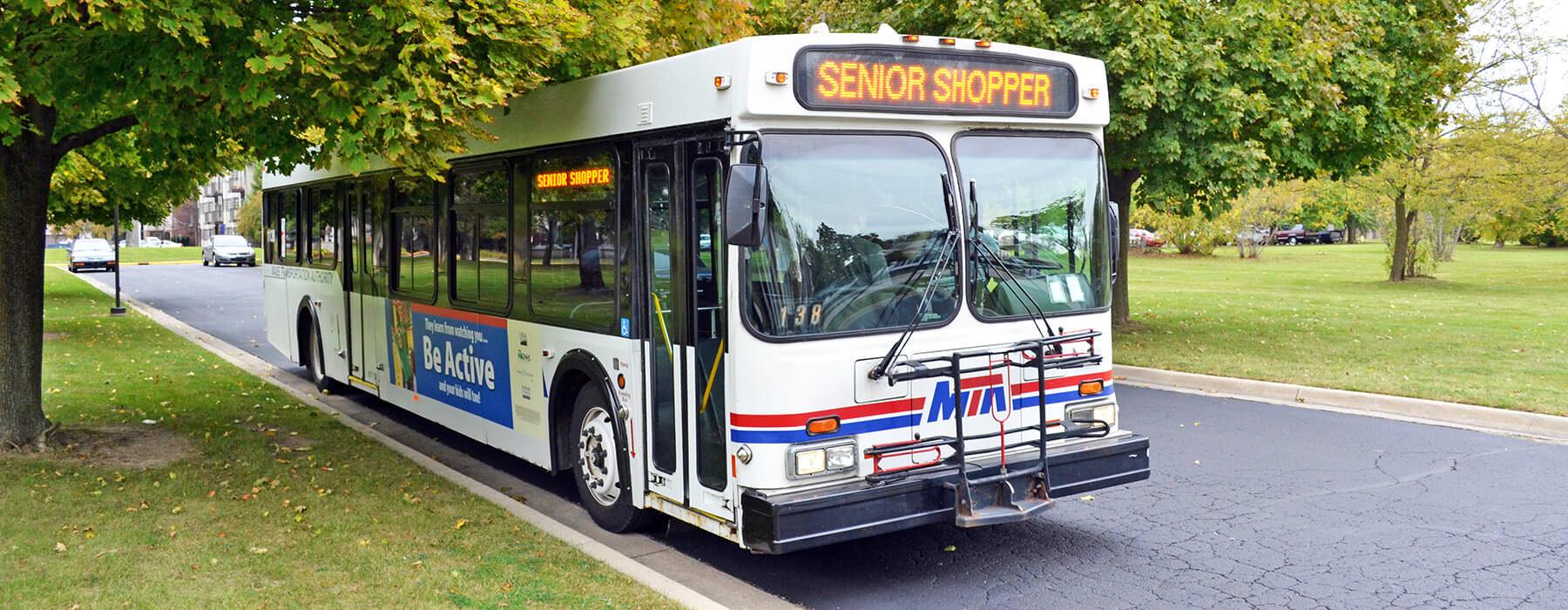 Senior Shopper bus on city street.