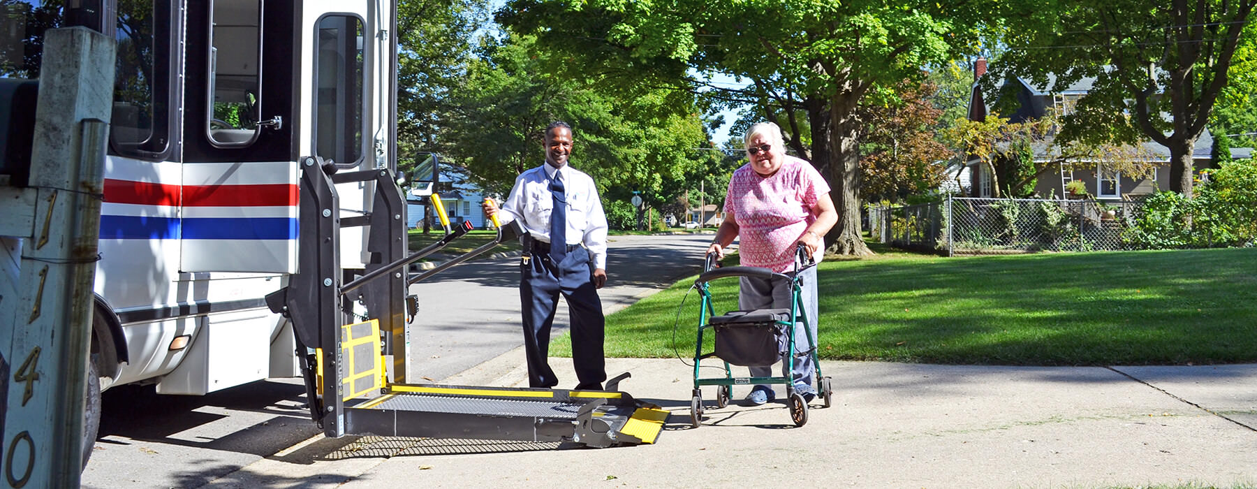 Elderly woman with walker boarding a Your Ride bus, assisted by the driver, via the wheelchair lift.